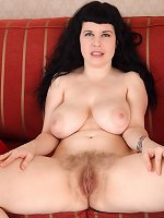 Suzie strips naked on her red sofa
